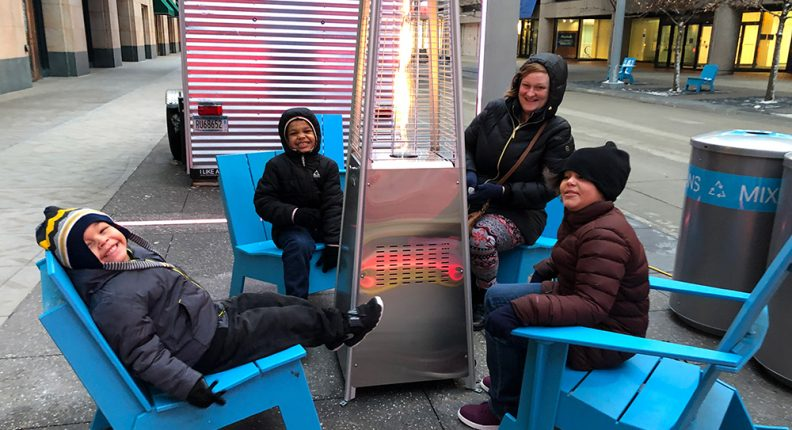 Mpls DID activating Nicollet Street with a family sitting around the heater